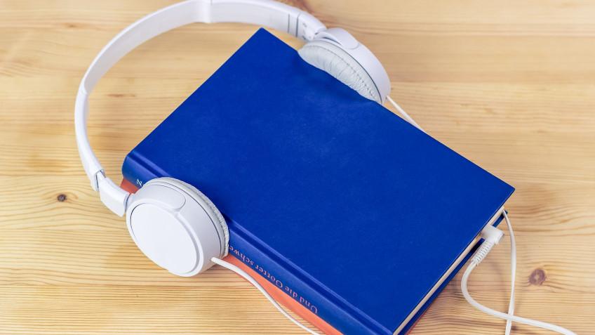 Libro con auricular colocado sobre él, simulando que el libro está escuchando un audio.