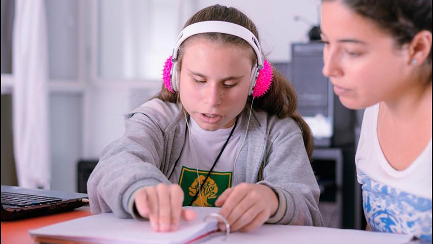 Una nena hace la tarea junto a su maestra